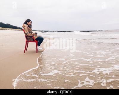 Donna seduta su una sedia in riva Foto Stock