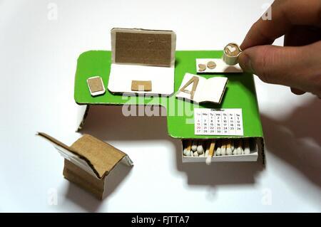 Immagine ritagliata della mano azienda piccola tazza di caffè sul piccolo Desk contro uno sfondo bianco Foto Stock