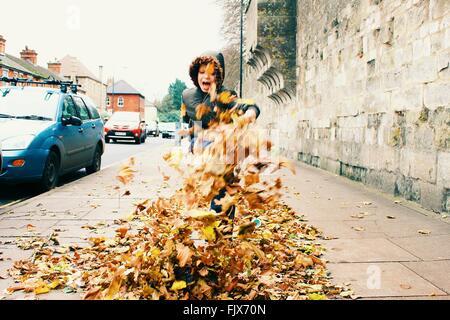 Giocoso ragazzo calci su foglie secche in marciapiede durante l'Autunno Foto Stock
