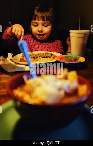 Ragazza a mangiare cibo a casa Foto Stock