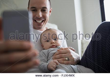 Sorridente padre e figlio bambino tenendo selfie Foto Stock