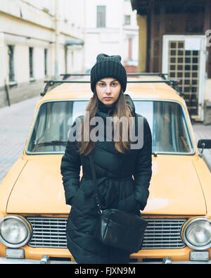 Ritratto di giovane e bella donna appoggiata sulle auto parcheggiate lungo la strada Foto Stock
