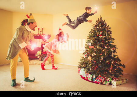 Digital immagine composita della famiglia felice decorazione albero di Natale a casa Foto Stock
