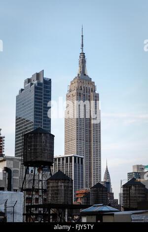 In legno antico deposito di acqua di torri in giustapposizione con moderni grattacieli come Empire State building Foto Stock