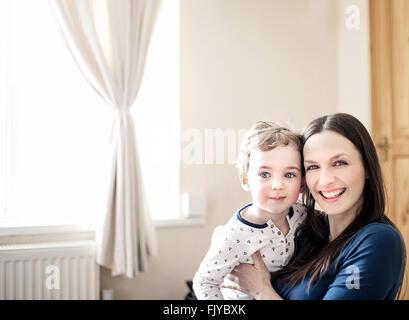 Giovane mamma con il suo piccolo ragazzo in armi a casa Foto Stock