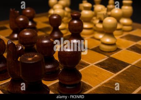 Luce e legno scuro pedine sulla tavola scacchi. Immagine ad alta risoluzione. Foto Stock