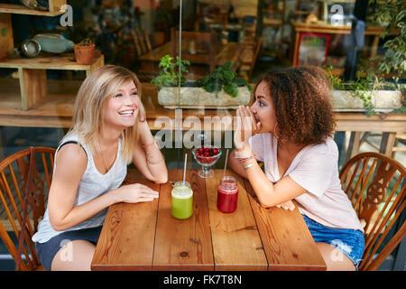 Giovani amici di sesso femminile avente pettegolezzi privato al cafè sul marciapiede. Due giovani donne spettegolare Foto Stock