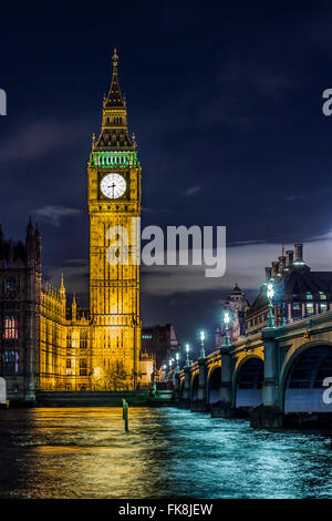 La bellissima Elizabeth Tower con le campane del Big Ben in alto e il Parlamento nei pressi di un ponte sopra il fiume Tamigi a Londra di notte. Foto Stock