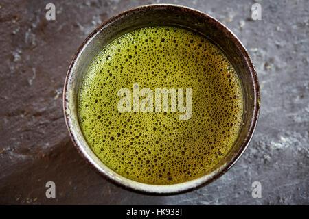Verde matcha tè con bolle sopra vista con frusta e polvere e cucchiaio Foto Stock