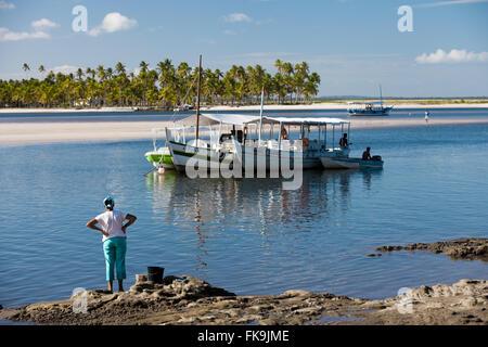 Barche ormeggiate in mare e alberi di noce di cocco in background nel villaggio di Boipeba - Arcipelago Tinhare Foto Stock