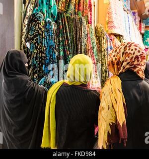 Tre donne, 1 in chador e 2 in testa colorate sciarpe panno di esplorazione per la vendita in Vakil Bazaar, Shiraz, Foto Stock