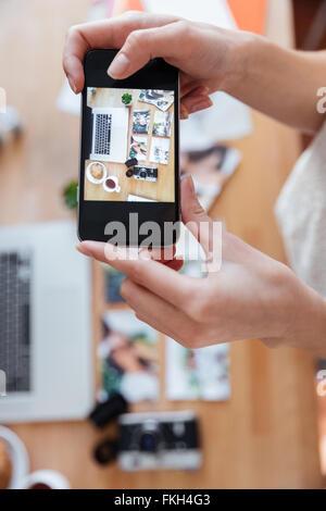 Primo piano delle mani della giovane donna di scattare le foto di oggetti sul suo posto di lavoro utilizzando lo Foto Stock