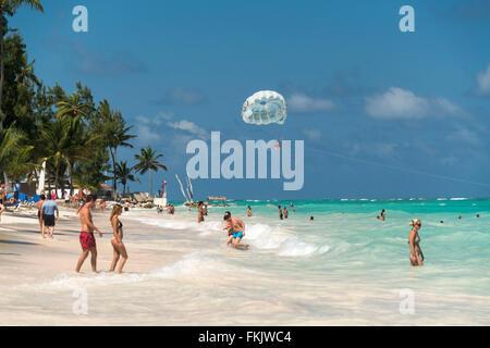 Il parasailing al orlata di palme sulla spiaggia di sabbia di Playa Bavaro, Punta Cana, Repubblica Dominicana, Caraibi, Foto Stock