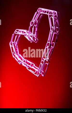 Il cuore da graffette su uno sfondo rosso Foto Stock
