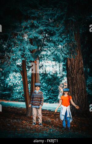 Razza mista bambini utilizzando la realtà virtuale occhiale all'aperto Foto Stock