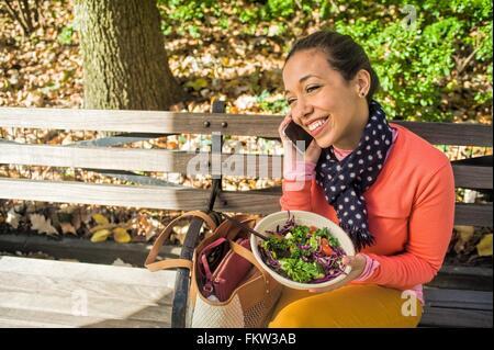 Giovane donna seduta su una panchina nel parco chiacchierando sullo smartphone mentre si mangia il pranzo Foto Stock