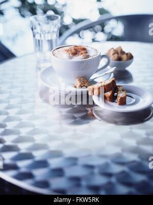 Tazza di cappuccino, biscotti sul tavolo Foto Stock