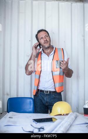 Metà maschio adulto costruzione foreman parlando su smartphone a scrivania in cabina portatile Foto Stock