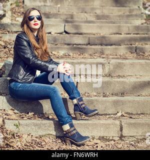 Giovane donna elegante in jeans e giacca di pelle in appoggio sul parco scale. Attraente ragazza con i capelli lunghi Foto Stock