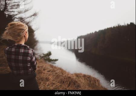Giovane donna in piedi sulla collina ammirando la splendida vista Foto Stock