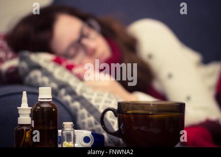 Malati donna che dorme nel letto accanto a pillole e farmaci Foto Stock