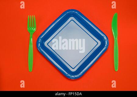 Piastra di colore blu su rosso con forcella cucchiaio coltello Foto Stock
