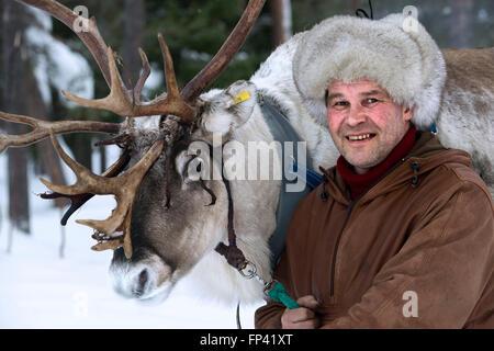 Ritratto di un pastore con la sua renna. Fattoria di renne nella Salla, Lapponia finlandese. La renna è una icona Foto Stock