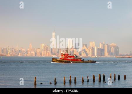 New York inferiore dello skyline di Manhattan con un rimorchiatore a traino e il quartiere finanziario di grattacieli Foto Stock
