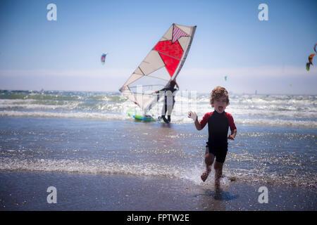 Piccolo bambino correre sulla spiaggia e padre in background di Viana do Castelo, Regione Norte, Portogallo Foto Stock