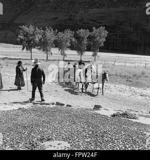 1930 un gruppo di nativi americani indiani navajo mais di essiccazione a guardare la donna di equitazione per bambini Foto Stock