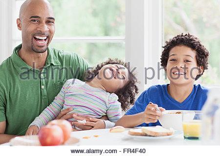 Bello padre e figli giovani al tavolo per la colazione Foto Stock