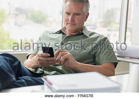 Imprenditore rilassato sms sul cellulare in ufficio. Foto Stock