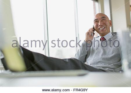 Coppia asiatica di imprenditore con piedi sulla scrivania. Foto Stock