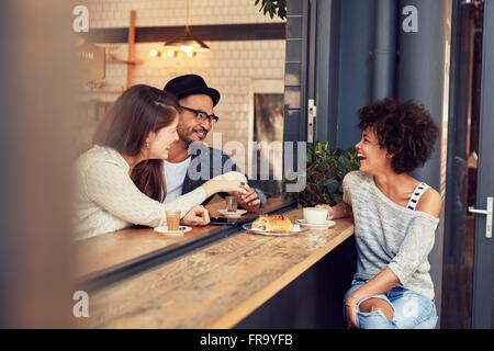 Ritratto di felice giovani seduti insieme ad un cafe avente un po' di cibo e caffè. Gruppo di amici riuniti in un Foto Stock