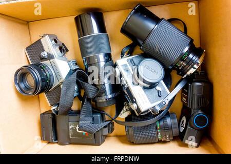 Una raccolta di vecchie 35mm Pellicola fotocamere, obiettivi e flash pistole per la vendita su un mercato delle Foto Stock