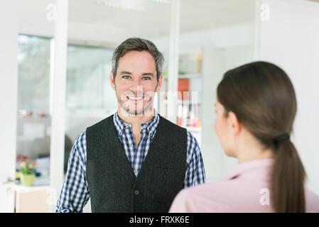 Ritratto di quaranta anni vecchio uomo con i capelli grigi e la barba che indossa un a scacchi in maglietta blu. Foto Stock