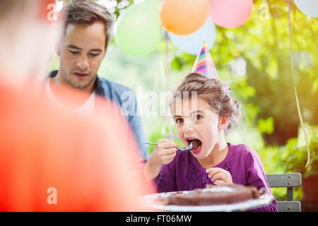 Garden party di Condivisione in famiglia la torta di compleanno di sette anni sta godendo del suo pezzo, il giardino Foto Stock