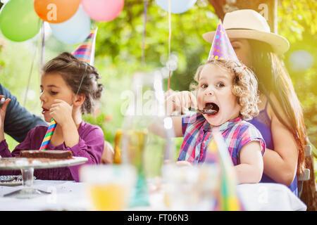 Garden party di Condivisione in famiglia la torta di compleanno. I tre anni sta godendo del suo pezzo, il giardino Foto Stock