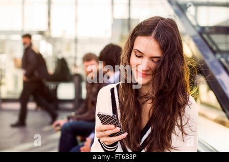 Bella imprenditrice utilizzando il telefono cellulare al di fuori dalla stazione ferroviaria Foto Stock