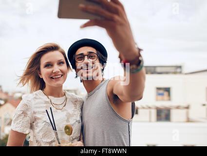Due giovani amici prendendo autoritratto con smart phone durante una festa. Giovane uomo e donna prendendo selfie Foto Stock