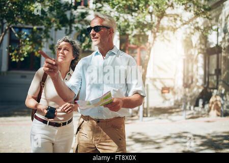 Coppia matura tourist esplorare una città estera. Coppia senior usando la mappa e cercando la direzione. Foto Stock