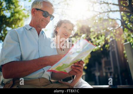 Coppia senior insieme nella città guardando alla mappa per raggiungerci. Uomo maturo e per donne che utilizzano Foto Stock