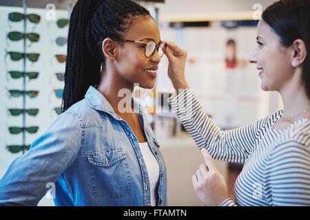 All'ottico optometrista aiutando un grazioso client africana di provare e acquistare telai per un paio di occhiali Foto Stock