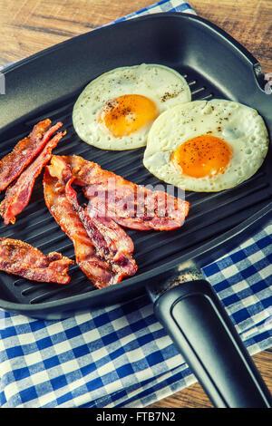 Prosciutto e uova. Uova e pancetta. Uovo salato e cosparsi di pepe nero. Prima colazione inglese. Bacon arrosto, Foto Stock