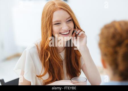 Allegro redhead piuttosto giovane donna seduta e ridere con il suo amico in cafe Foto Stock