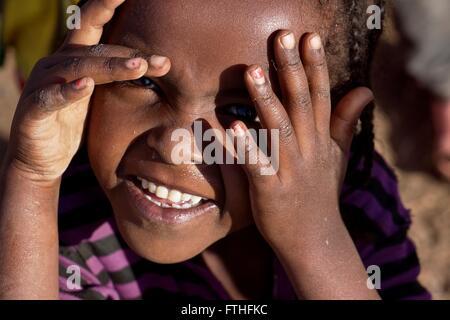 Giovane ragazza etiope che copre gli occhi dal sole Foto Stock