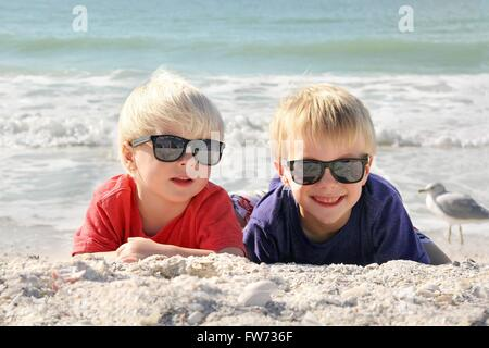 Due giovani felici i bambini, un ragazzino e il suo bimbo piccolo fratello, si posa sulla spiaggia di sabbia bianca Foto Stock
