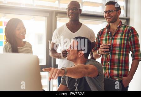 Bel giovane adulto che mostra qualcosa sul suo computer a un gruppo di tre maschi e femmine vestiti casualmente Foto Stock
