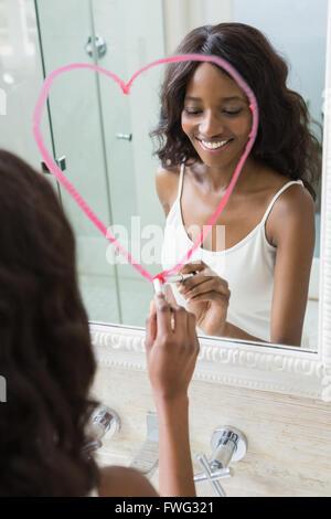 Bella giovane donna disegno grande cuore sullo specchio Foto Stock