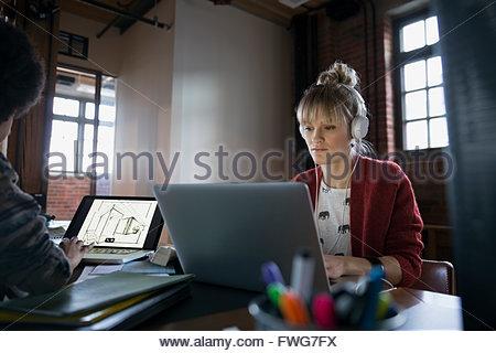 Designer con cuffie utilizzando computer portatile in ufficio Foto Stock
